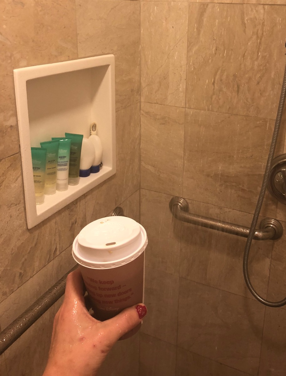 Amelia holding a coffee in the shower